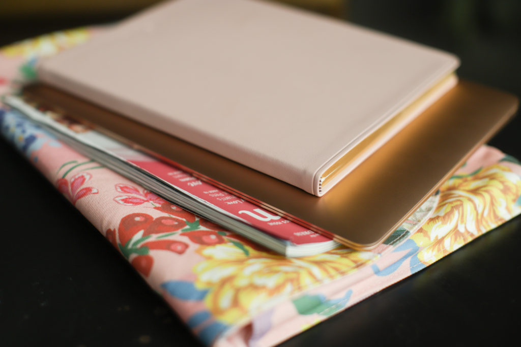A pink journal on top of a closed rose gold laptop on top of a magazine with a pink cover, all stacked on a floral laptop carrier.