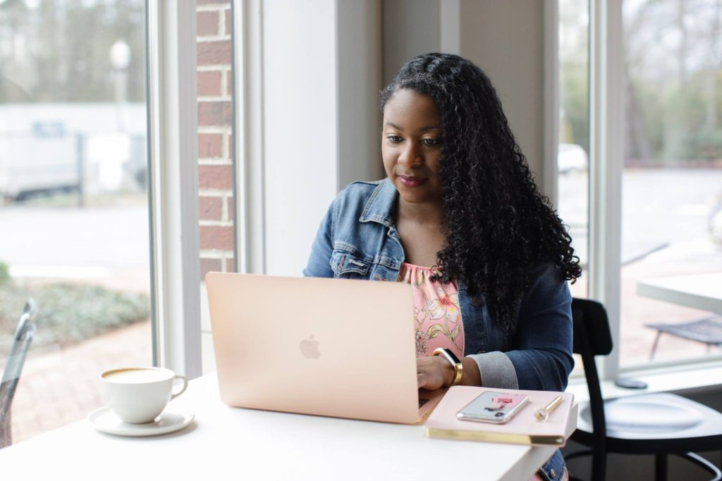 An African-American woman (me!) sitting at a table typing at arose gold laptop. A pink journal, cell phone, pen, and cup of coffee are on the table, too.